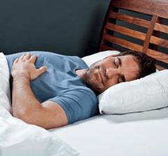 Ein Mann schläft in einem Bett