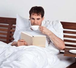 Mann trinkt in einem Bett einen Kaffee und liest dabei ein Buch