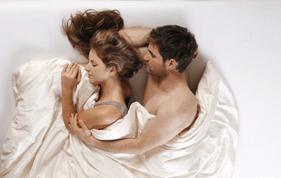 Frau und Mann schlafen in einem Bett