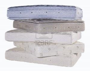 Auf dem Bild sieht man mehrere, übereinander gestapelte Matratzen.