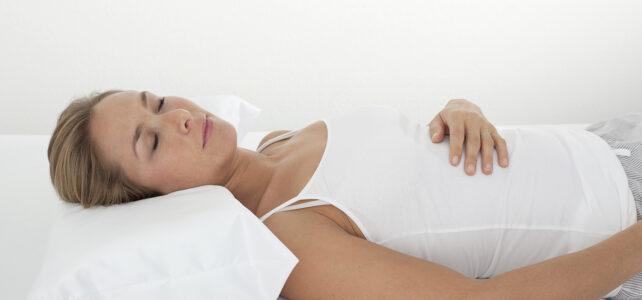 Frau liegt in der Rückenlage auf einem Nackenstützkissen